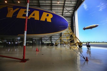 The Spirit of Innovation is on the ground still in the hangar as The Spirit of Goodyear flies overhead.  Photo: Mike Stocker / Sun Sentinel