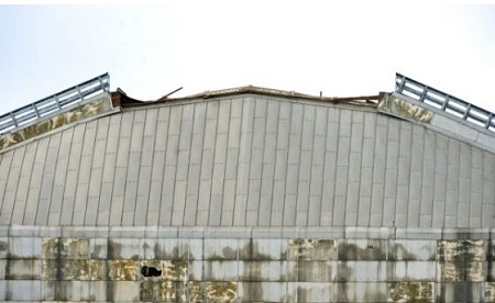 A section of a walkway on the top of the North Tustin blimp hangar collapsed, sending debris down on the Aeroscraft, an experimental helium-filled craft being developed to ferry cargo. The partial roof collapse was reported at 7:45 a.m. Monday at the former base, said Capt. Steve Concialdi of the Orange County Fire Authority. Photo: Sam Gangwer, Orange County Register