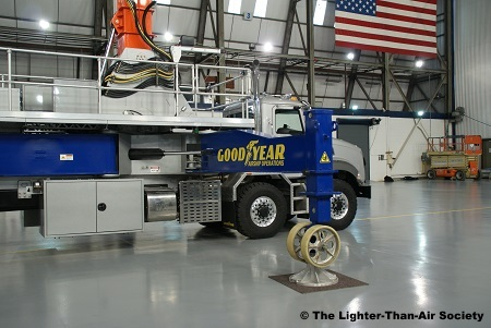 The mast truck is equipped with two outriggers on each side to stabilize it.  When deployed in an X formation, the truck and blimp can withstand winds of up to 90 mph.