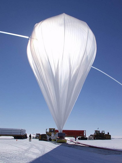 High-pressure helium from Kelly trucks carrying gas cylinders rushes through fill tubes extending from the top of a balloon that is pinned to the ground by a spool truck. The rest of the balloon's flight train is laid out on the ground to the right. The photos in this article were taken during several different balloon campaigns, this one in Antarctica. Photo: NASA