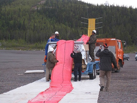 The fan-folded balloon is delivered to the launch site in an enormous crate. Here the crew is carefully pulling it from the crate and laying it onto a protective tarp prior to launch.  Photo: NASA