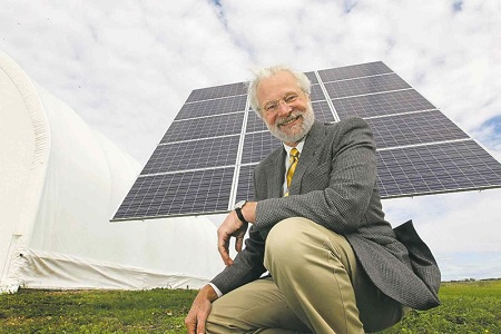 Barry Prentice crouches next to a new solar-power system installed at the BASI hangar, which currently provides heat and light for the operation.  Photo: Ruth Bonneville - Winnipeg Free Press
