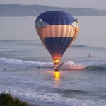 Hot air balloon dips close to the ocean