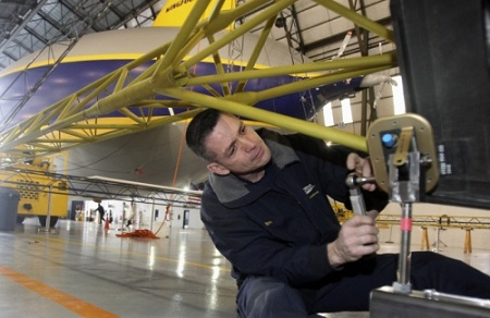 Tom Bradley Goodyear airship fabrication mechanic works on a longeron for the second of three semirigid airships at the Goodyear Airship base in Suffield Township on Friday. Goodyear has started building the airships. Goodyear's first zeppelin Wingfoot One rests in the background.  Photo: Mike Cardew - Akron Beacon Journal