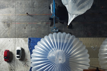 Among the upgrades Google is testing for its balloons (seen here from the rafters): using hydrogen, which is cheaper than helium, and having a motor move their solar panels to track the sun. Image courtesy of MIT Technology Review
