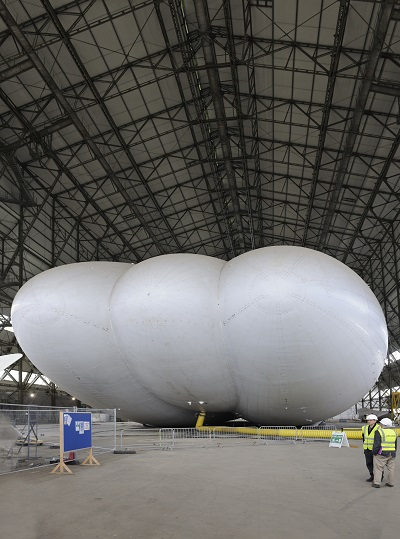 A yellow air duct keeps the Airlander 10 inflated for now, though helium will be pumped in later this year. The aft end, visible in this view, will house propulsors and tail units on the end of the outer lobes.  Credit: Mark Wagner, Aviation-Images.com