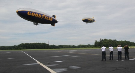 The ground crew watches as the Goodyear airships Spirit of Innovation (left) and Wingfoot One take flight at the company's airship base in Suffield Township on Wednesday.  Photo: Michael Chritton/Akron Beacon Journal
