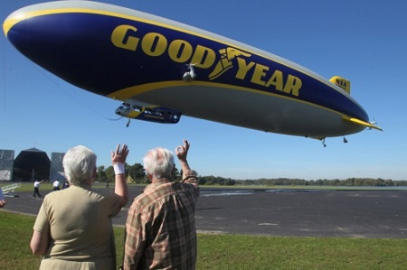 In this Spt. 2014 file photo, Charlotte White, who won the national contest to name the newest airship, and her husband Eugene, wave to the friends on the blimp after they took the first ride on Wingfoot One at the Goodyear Airship base in Suffield Township. Photo: Mike Cardew/Akron Beacon Journal file.