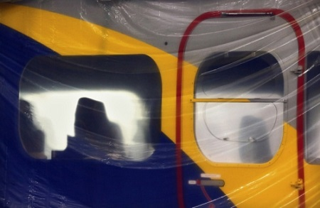 The gondola of Goodyear's new airship is protected by plastic as employees with Thomarios in Copley, apply another coat of blimp blue V2.  Photo: Ed Suba Jr. - Akron Beacon Journal.