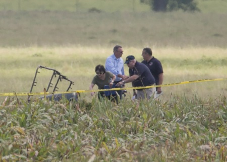"The partial frame of a hot air balloon is visible above a crop field as investigators comb the wreckage of a crash Saturday morning, July 30, 2016, near XXX, Texas. Authorities say the accident caused a ""significant loss of life."" Image: Ralph Barrera/Austin American-Statesman via AP."