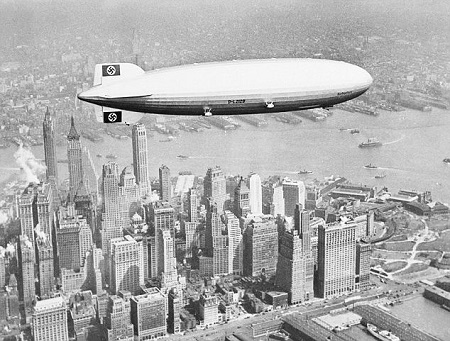 Swastikas over Manhattan: The Hindenburg flies over New York on her first visit to North America in May 1936. Past the tail of the zeppelin is the Bank of Manhattan Building and the City Service Building