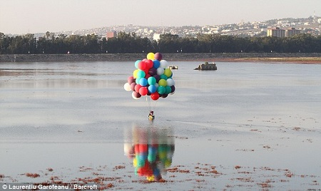 Jonathan Trappe and co-pilot Nidia Ramirez make sure the boat can land efficiently - done so by cutting away at some of the balloons.  Photo: Laurentiu Garroteanu/Barcroft  on DailyMail.co.uk