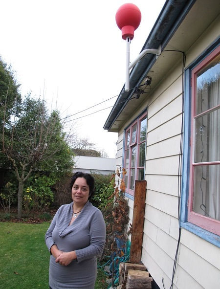 Tania Gilchrist stands outside her home below a red Google Internet receiver after agreeing to participate in Google's balloon testing program in Christchurch, New Zealand, Friday, June 14, 2013. Google is testing balloons which sail in the stratosphere and beam the Internet to Earth.  (AP Photo/Nick Perry)