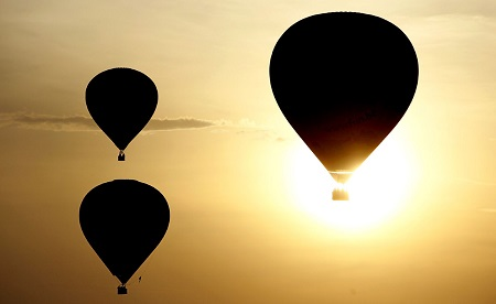 Hot air balloons are backlit by the rising sun.  Photo: AP Mathieu Cugnot