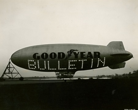 Goodyear blimp Puritan uses its Trans-Lux sign to flash a special bulletin from the Beacon Journal newsroom in 1947. Goodyear called the process  blimpcasting.  The letters were 18 feet high. Credit: Akron Beacon Journal