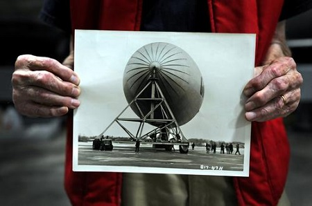 Russ Magnuson of Southington, holds a photo from 1947 of the Goodyear ZNPK-28 Blimp Control Car and the giant gas envelope that holds it up. Magnuson and a small group of volunteers have been restoring the blimp car for the past 21 years at the New England Air Museum.