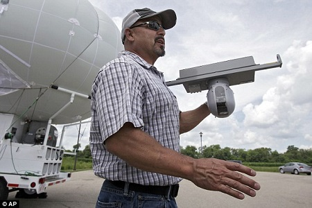 Similar to a weather balloon, the blimp can hover silently in the air for up to three days at a time, while capturing video footage. Above, an official shows off one of the device's heat sensors. Photo courtesy of The Daily Mail