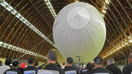 Employees of Worldwide Aeros Corp. watch the dedication of the Aeros 40D Sky Dragon airship in a World War II-era blimp hangar in Tustin.  Photo: Don Bartletti - Los Angeles Times
