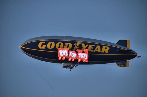 """The Goodyear Tire & Rubber Company's blimp """"Spirit of Goodyear"""" displays the U.S. Marine Corps Reserve's Toys for Tots logo on its electronic sign. Photo courtesy of Goodyear Tire 7 Rubber Co."""
