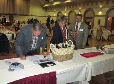 LTAS member Ron Syroid (L) examines an auction item, while members Trey and Rachel Wackerly discuss their bid.