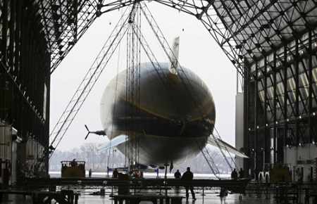 Triangular shaped section 5 consisting of frames 4 and 5 of the new airship can be seen suspended in hangar as Wingfoot One heads out for a flight at the Goodyear Airship base in Suffield Township on Friday. Goodyear has started building the second of three semirigid airships.  Photo: Mike Cardew - Akron Beacon Journal