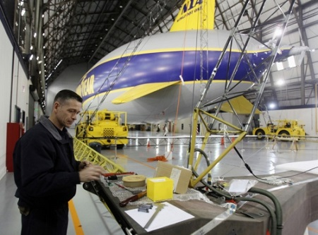 Tom Bradley Goodyear airship fabrication mechanic works on the second of three semirigid airships at the Goodyear Airship base in Suffield Township on Friday. Goodyear WIngfoot One is in the background.  Photo: Mike Cardew - Akron Beacon Journal
