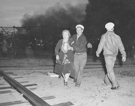 Seelig-Hoff photo. Sailor from the naval airfield assists a woman survivor to first aid station after the Hindenburg dirigible disaster. Courtesy of the New York Daily News