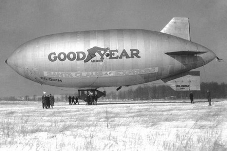 Goodyear's Pilgrim, built in 1925, was the first commercial non-rigid airship flown using helium and Goodyear's first promotional blimp. Here it is made up as the Santa Claus Express circa 1927.