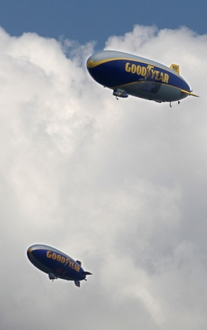 Goodyear Zeppelin Wingfoot One (top) and Goodyear Blimp Spirit of Innovation fly over Stan Hywet Hall for Community Day during its 100th anniversary celebration on Sunday in Akron. Photo: Mike Cardew/Akron Beacon Journal