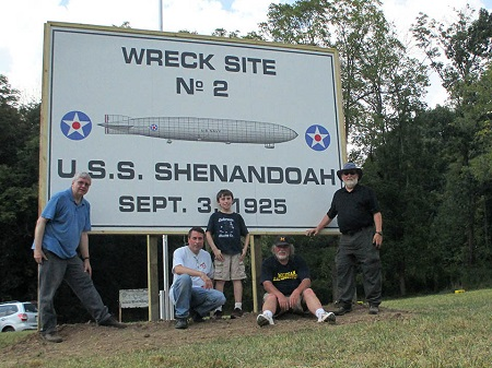 The new sign for Crash Site 2 erected by (l to r) Eric Brothers, Wayne Buchanan, Nikolas Buchanan (ladder holder and tool facilitator), John Cunningham and Dave Wertz. Note in the background, the old sign that has been replaced. Photo: Eric Brothers.