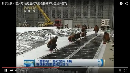 By the Power of the Sun Solar panels lie on the hangar floor, ready to be attached to the Yuanmeng once it's fully inflated. Image: NNTV