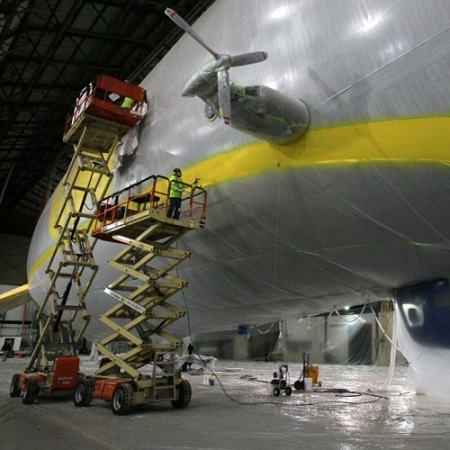Jim Westfall, an employee with Thomarios in Copley, applies yellow paint to a detail line on Goodyear's new airship.  Photo: Ed Suba Jr. - Akron Beacon Journal.