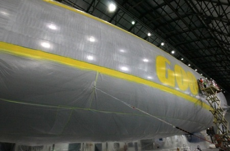 Gary Hagan (left) and Josh Scharfenberg, employees with Thomarios in Copley, apply yellow paint to lettering and lines on Goodyear's new airship. Photo: Ed Suba Jr. - Akron Beacon Journal.
