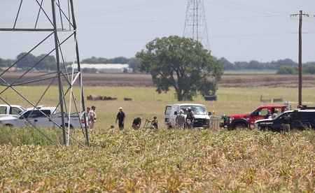 "Investigators surround the scene in a field near Lockhart, Texas where a hot air balloon carrying at least 16 people collided with power lines Saturday, July 30, 2016, causing what authorities described as a ""significant loss of life."" Image: Ralph Barrera/Austin American-Statesman via AP."
