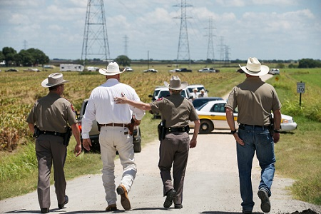 Texas DPS Trooper Robbie Barrera, center right, puts her arm around Caldwell County Sheriff Daniel Law as he arrives on the scene of a hot air balloon crash. Image: Ralph Barrera/Austin American-Statesman via AP)