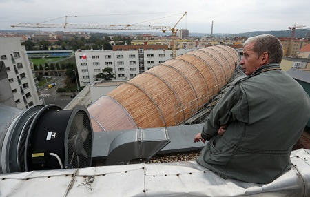 Leos Valka, a co-creator, sits on a rooftop overlooking a giant object resembling a zeppelin airship at an arts center in Prague, Czech Republic. The 42-meter long and 10-meter wide ship is planned to seat some 120 people on its cascade steps. It will be used for authors' reading and debates about literature to complement exhibitions at the DOX Centre for Contemporary Art, one of the most innovative and challenging galleries in the Czech capital. Photo: Petr David Josek, AP